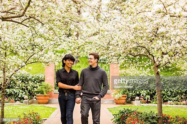 Couple walking under flowering trees in park