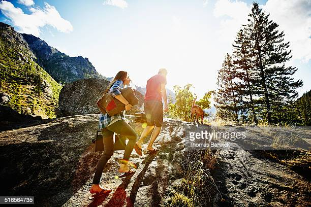 Couple walking up rocky slope in wilderness