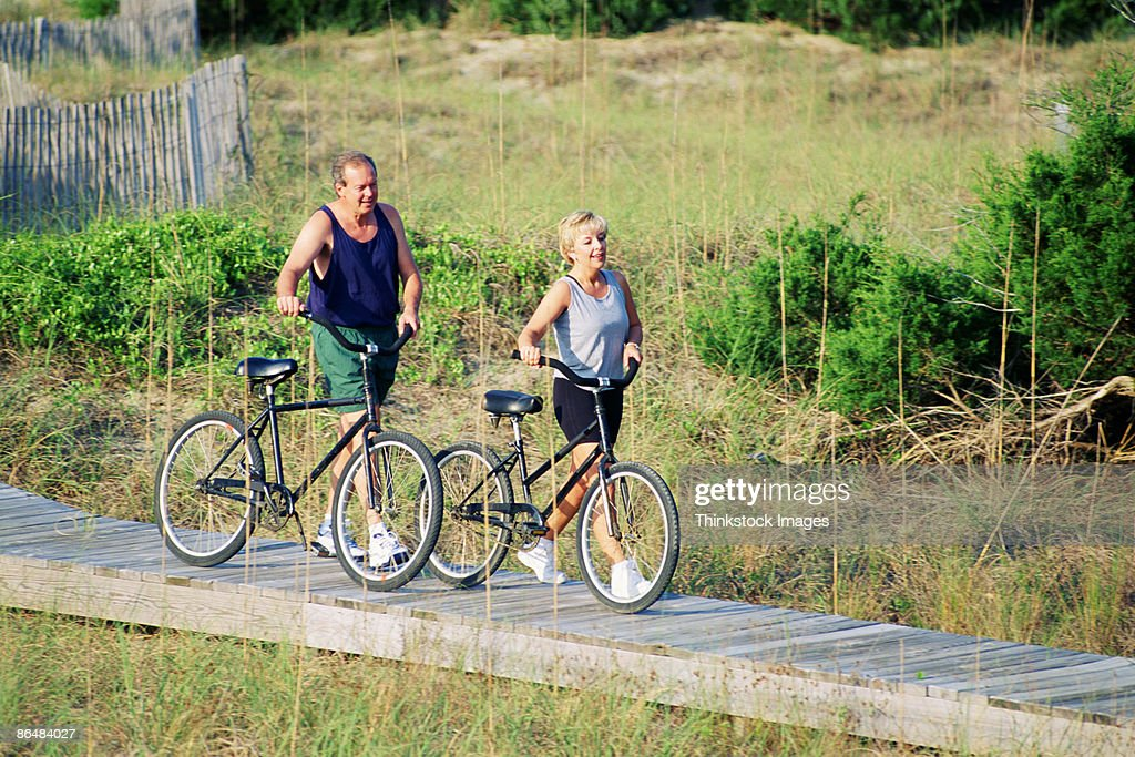 Couple walking with bicycles : Stock Photo