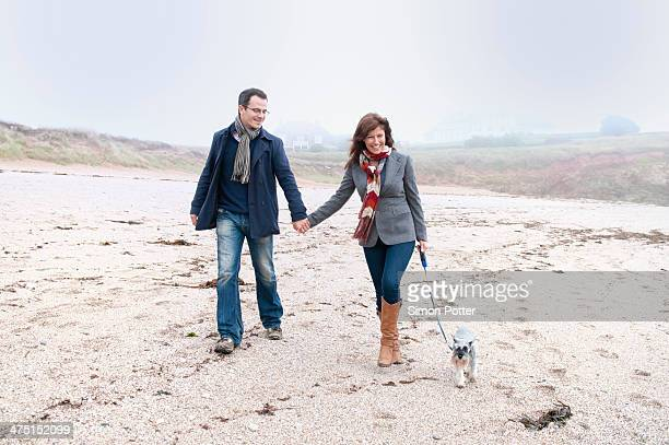 Couple walking with dog on beach, Thurlestone, Devon, UK