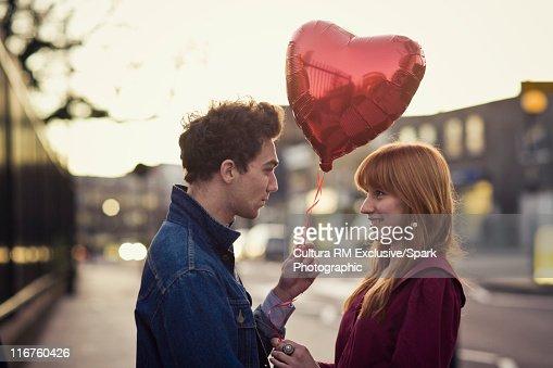 Couple walking with heart-shaped balloon : Stock Photo