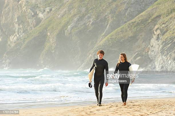 Couple walking with surfboards along beach.