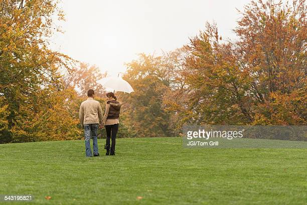 Couple walking with umbrella in park