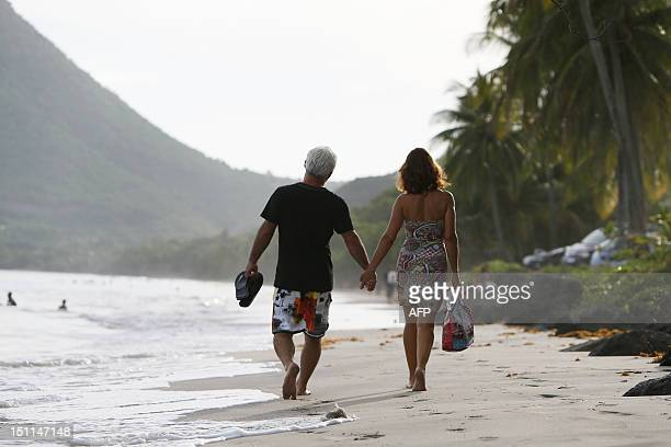 A couple walks along a beach in Le Diamant in the French Caribbean island of La Martinique on September 1 2012 AFP PHOTO KENZO TRIBOUILLARD