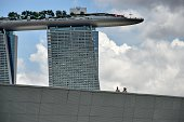 A couple walks along the Marina barrage next to the Marina Bay Sands hotel resorts in Singapore on August 11 2014 Singapore's tradesensitive economy...