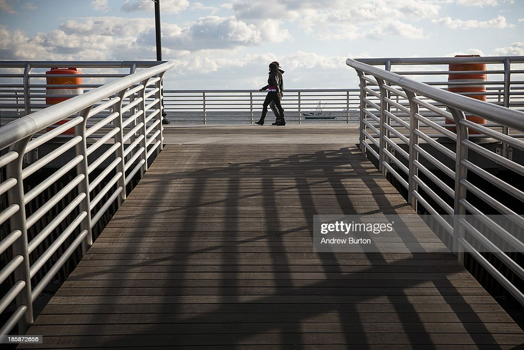 A couple walks along the newly reopened boardwalk on October 25, 2013 in Long Beach, New York. The boardwalk was severely damaged by Superstorm Sandy last year, which killed 285 people and caused billions of dollars in damage. Long Beach's new boardwalk is made of Brazilian hardwood and is estimated to have a lifespan of 30-40 year; the previous boardwalk was only scheduled to last three to seven years.