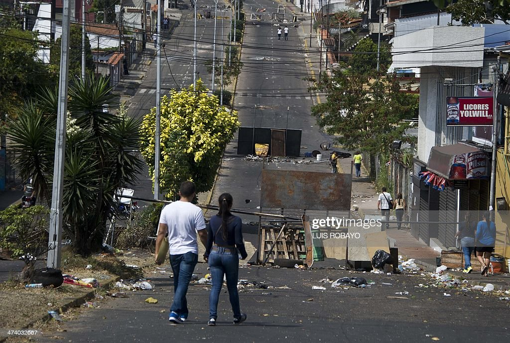 A couple walks amidst barricades in the streets of San Cristobal, capital of the western border state of Tachira, Venezuela, on February 21, 2014. At least eight people have been killed, 137 wounded and more than 100 detained in the protests shaking Venezuela, officials said Friday, confirming a jump in the death toll. AFP PHOTO/Luis ROBAYO