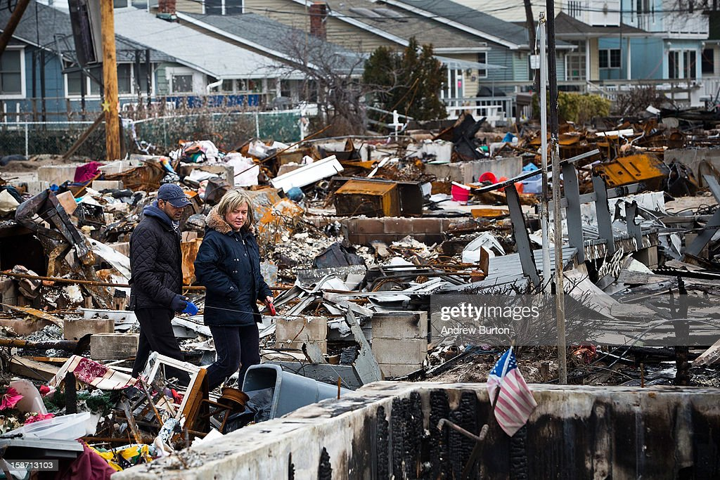 A couple walks amongst the remains of burned houses in the Breezy Point neighborhood of the Borough of Queens on December 25, 2012 in New York City.