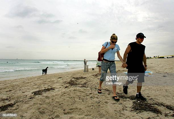 A couple walks away from the water shortly after a Chalk's Seaplane burst into flames and plunged into the Atlantic Ocean December 19 2005 in Miami...