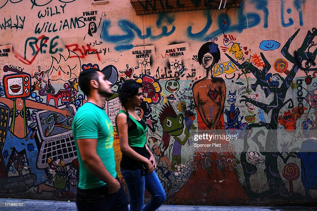 A couple walks by a colorful mural in a fashionable neighborhood on June 29, 2013 in Beirut, Lebanon. Currently the Lebanese government officially hosts 546,000 Syrians with an estimated additional 500,000 who have not registered with the United Nations. Lebanon, a country of only 4 million people, is now home to the largest number of Syrian refugees who have fled the conflict. The situation is beginning to put a huge social and political strains on Lebanon as there is currently no end in sight to the war in Syria.