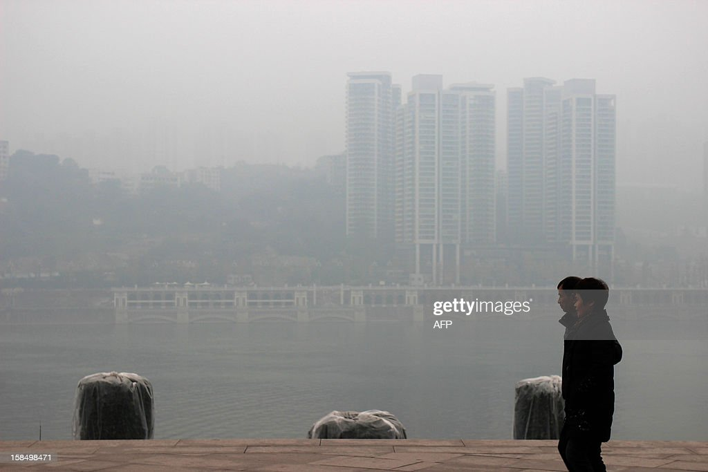 A couple walks by a river in Chongqing under dense fog on December 18, 2012. The cost of new homes increased in more Chinese cities in November than in the previous month, official figures showed on December 18, despite efforts from the government to keep the market in check. CHINA