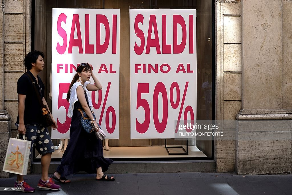 A couple walks by shop windows advertising sale on July 6, 2014 in downtown Rome, as Italian retailers started their summer sales. AFP PHOTO / FILIPPO MONTEFORTE