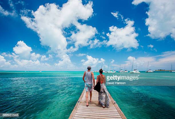 ANEGADA ISLAND, BRITISH VIRGIN ISLANDS, CARIBBEAN. A couple walks down a long dock surrounded by teal sea and blue sky.