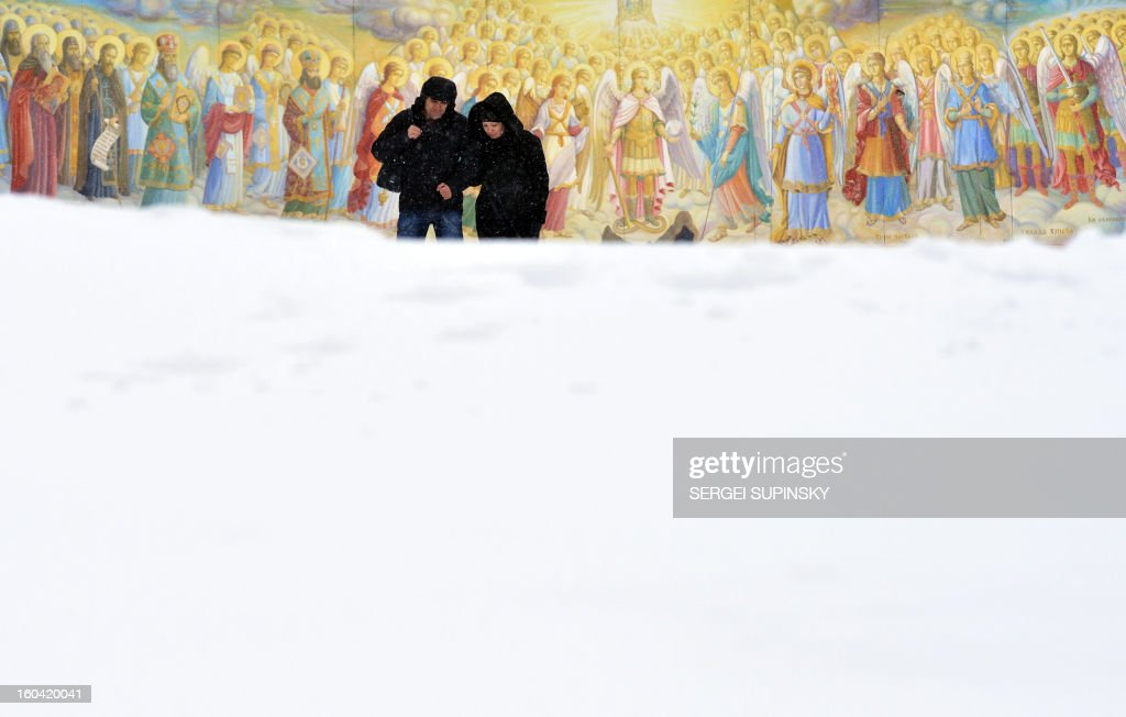 A couple walks during heavy snow fall in front of frescos of Mykhaylo Gold Domes Cathedral in the center of the Ukrainian capital of Kiev on January 31, 2013.
