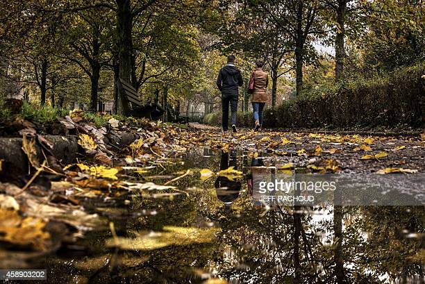 A couple walks in a park in Lyon centraleastern France on November 13 2014 AFP PHOTO / JEFF PACHOUD