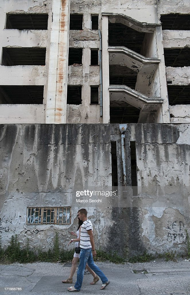 A couple walks in front of a building damaged by bulletts as the city of Mostar remembers the 1993 conflict on June 28, 2013 in Mostar, Bosnia and Herzegovina. The Siege of Mostar peaked in 1993 during the Croat-Bosniak conflict lasting eighteen months as fighting took place as Bosnia and Herzegovina declared independence from Yugoslavia. The city was divided in half between the two battling armies. Mostar, dating back over four hundred years, was mostly destroyed through the fighting. Although reconstruction has slowly commenced in the last decades, evidence of the war remains in bullet ravaged buildings still standing throughout the city.