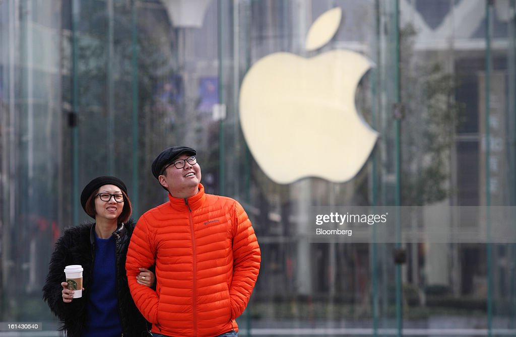 A couple walks in front of the Apple Inc. logo displayed at one of the company's stores in the Pudong area of Shanghai, China, on Saturday, Feb. 9, 2013. China's services industries grew at the fastest pace since August as gains in retailing and construction aid government efforts to drive a recovery in the world's second-biggest economy. Photographer: Tomohiro Ohsumi/Bloomberg via Getty Images
