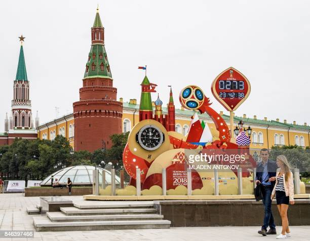 A couple walks in front of the digital FIFA World Cup 2018 countdown clock placed in front of the Red Square and the Kremlin in Moscow on September...