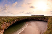 Couple walks in ocean in hidden beach w/rocky cove