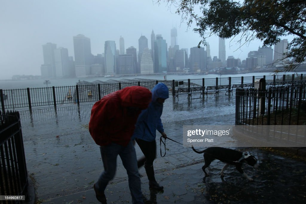 A couple walks in the rain as a darkened Manhattan is viewed after much of the city lost electricity due to the affects of Hurricane Sandy on October 30, 2012 in New York, United States. At least 33 people were reported killed in the United States by Sandy as millions of people in the eastern United States have awoken to widespread power outages, flooded homes and downed trees. New York City was his especially hard with wide spread power outages and significant flooding in parts of the city.