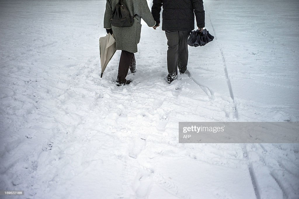 A couple walks in the snow in the city of Lyon on January 15, 2012. AFP PHOTO / JEFF PACHOUD
