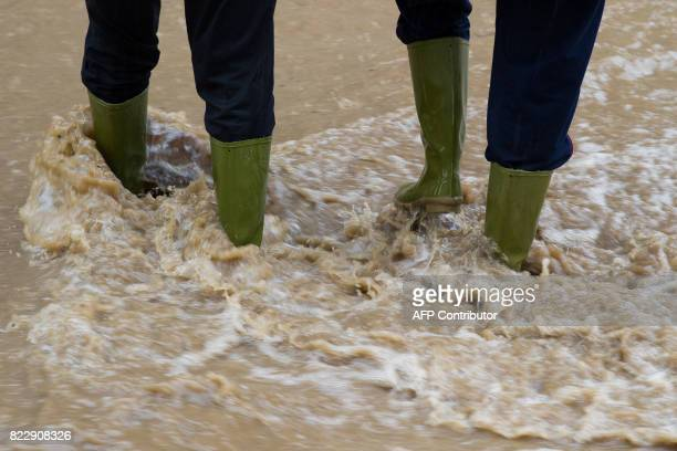 A couple walks on a flooded street in Bad Harzburg central Germany on July 26 2017 In some parts of Southern Lower Saxony rainfall has led to...