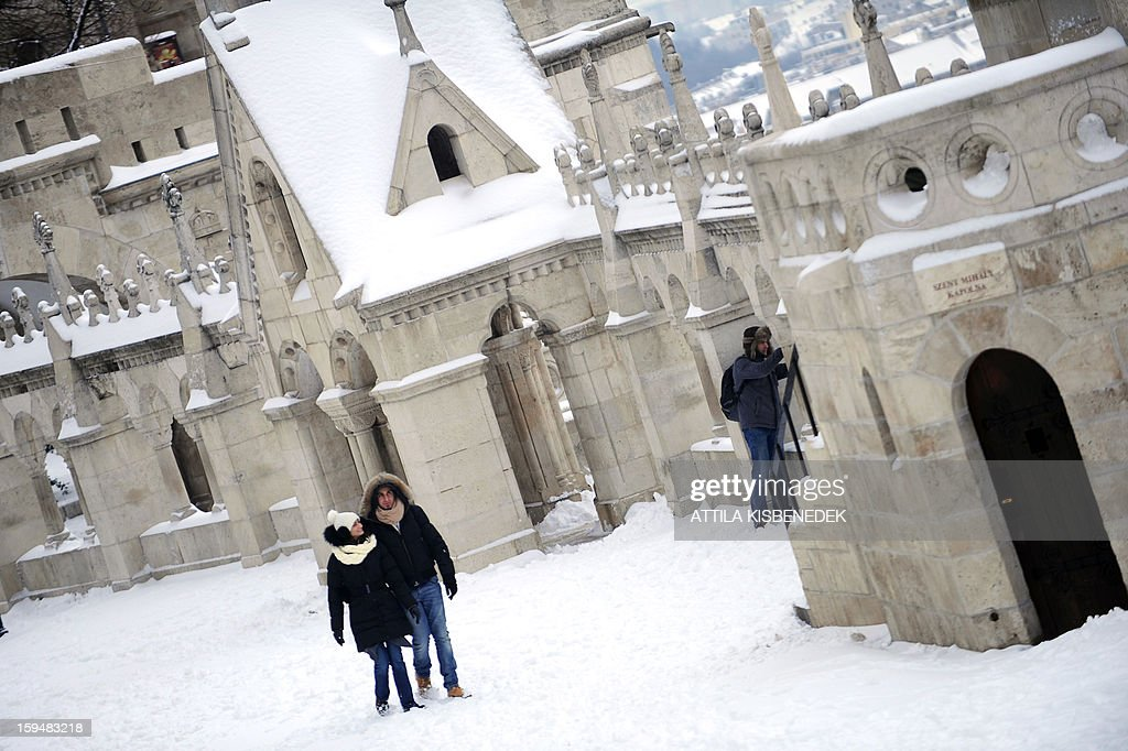 A couple walks on a snow covered street of the Fisher Bastion in Budapest, 1st district on January 14, 2013 as the Hungarian capital and several counties were hit by about 20 cm snow last night and this morning. The heavy snowfalls caused chaos in traffic and public transport. AFP PHOTO / ATTILA KISBENEDEK