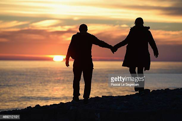 A couple walks on the beach at sunset on day six of the Sochi 2014 Winter Olympics on February 13 2014 in Adler Russia