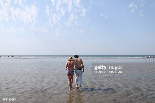 A couple walks on the beach of the French northwestern city of Deauville on July 1 as a blistering heatwave sweeps through Europe with temperatures...