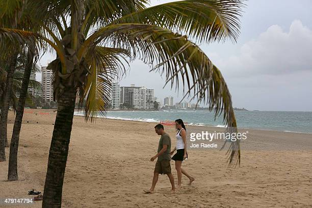 A couple walks on the beach on July 1 2015 in San Juan Puerto Rico The island's residents are dealing with increasing economic hardships and a...