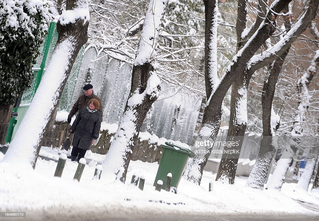 A couple walks on the snow and ice-covered pavement with her umbrella at the Buda Hill region of Budapest 12th district on March 26, 2013. Many parts of Europa are still covered in snow, less than a week before Easter.