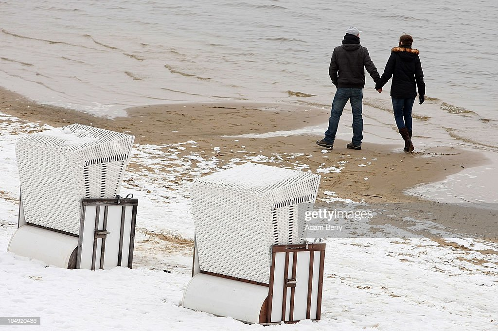 A couple walks on the snow-covered Strandbad Wannsee beach during its opening for the year on March 29, 2013 in Berlin, Germany. Despite continued unseasonably cold temperatures in the country, organizers opened the beach for bathers in time for the last weekend of March, when Easter Sunday is expected to be colder than the previous Christmas Day had been.