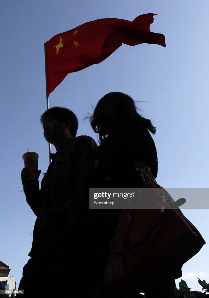 A couple walks past a Chinese national flag displayed outside a department store in Beijing, China, on Sunday, Nov. 11, 2012. China's retail sales exceeded forecasts and inflation unexpectedly cooled to the slowest pace in 33 months, signaling the government is boosting growth without driving a rebound in prices. Photographer: Tomohiro Ohsumi/Bloomberg via Getty Images
