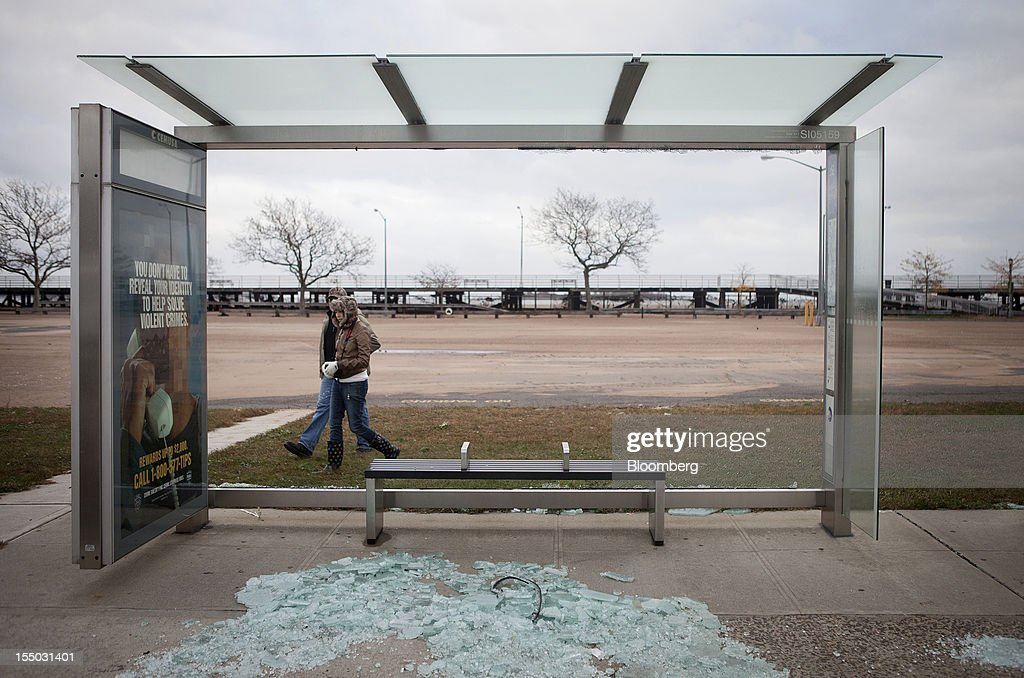 A couple walks past a damaged bus shelter as broken glass lies on the sidewalk in the Staten Island borough of New York US on Tuesday Oct 30 2012 New...