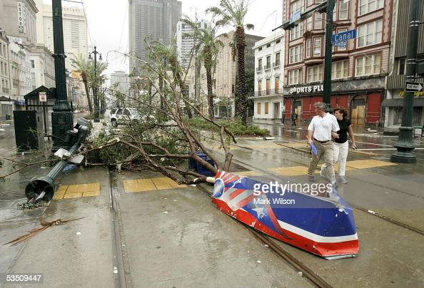 A couple walks past debris on Canal Street after Hurricane Katrina hit the area August 29 2005 in New Orleans Louisiana Katrina was down graded to a...
