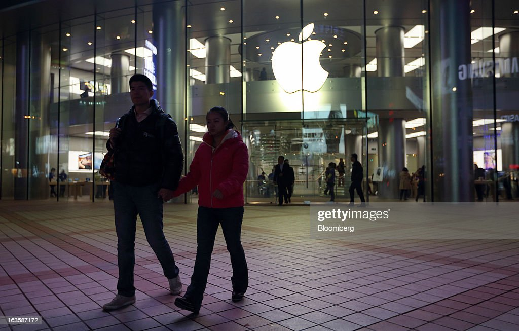 A couple walks past the Apple Inc. store in the Wangfujing area of Beijing, China, on Tuesday, March 12, 2013. Apple's Wangfujing store is the largest in Asia. Photographer: Tomohiro Ohsumi/Bloomberg via Getty Images