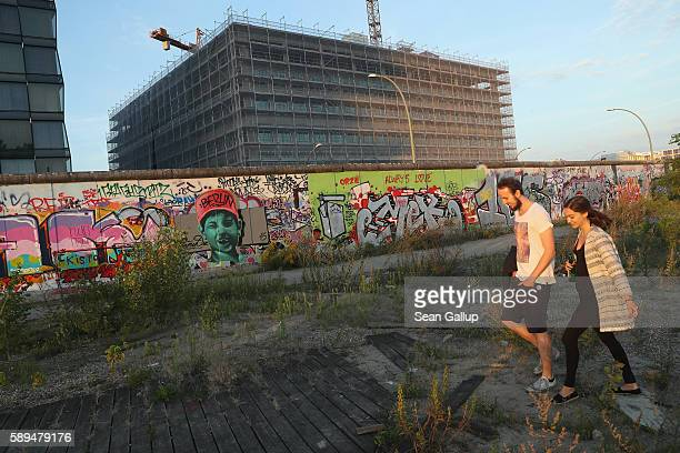 A couple walks past the East Side Gallery remnants of the Berlin Wall near a construction site on a warm summer evening on August 13 2016 in Berlin...