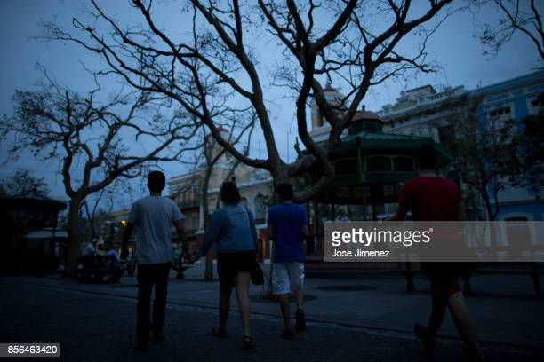 A couple walks past the Plaza de Armas on October 1 2017 in Old San Juan Puerto Rico Hurricane Maria caused extensive damage to the island as...
