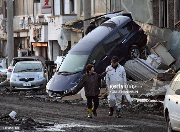 A couple walks past upturned vehicles sitting on a wall in the city of Miyako in Iwate prefecture on March 12 2011 a day after a massive 89 magnitude...