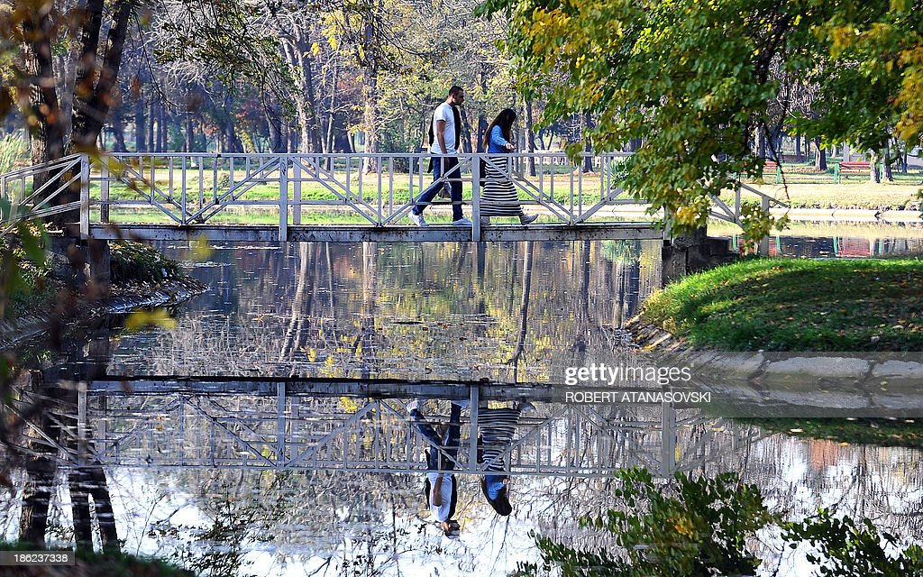 A couple walks through a autumnal coloured park during an unusually warm weather as temperatures reached 25 degrees Celsius, in Skopje on October 29, 2013.