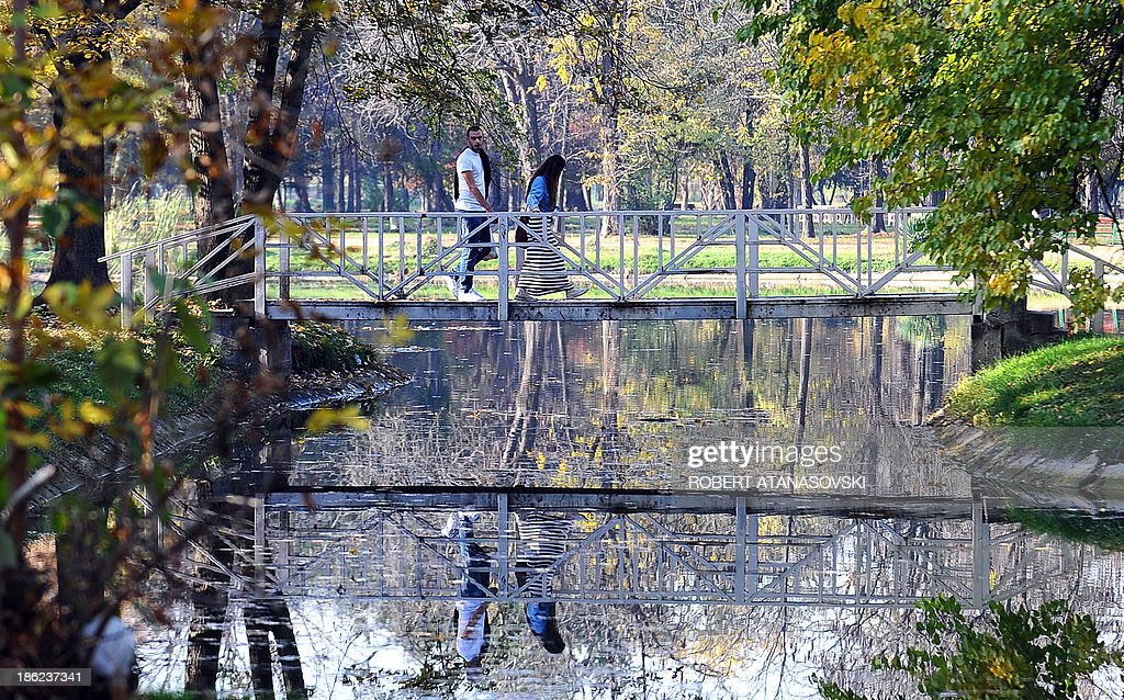 A couple walks through a autumnal coloured park during an unusually warm weather as temperatures reached 25 degrees Celsius, in Skopje on October 29, 2013. AFP PHOTO / ROBERT ATANASOVSKI