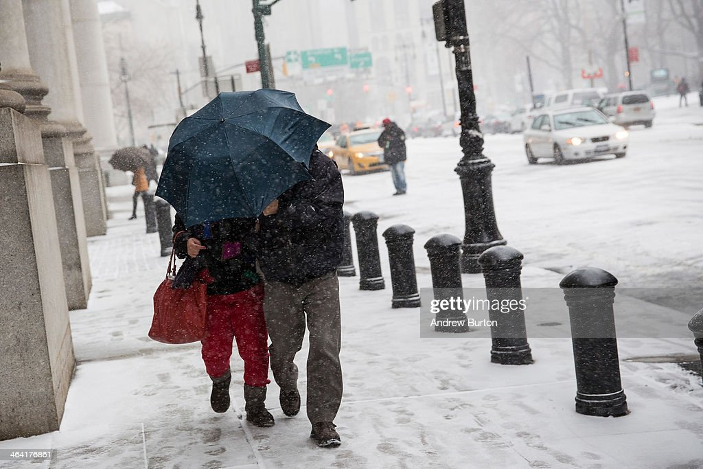 A couple walks through a snow storm that is moving through the Northeast on January 21, 2014 in New York City. Along with dropping arctic tempertures the storm is expected to bring three to five inches by nightfall, with another four to six inches falling overnight.