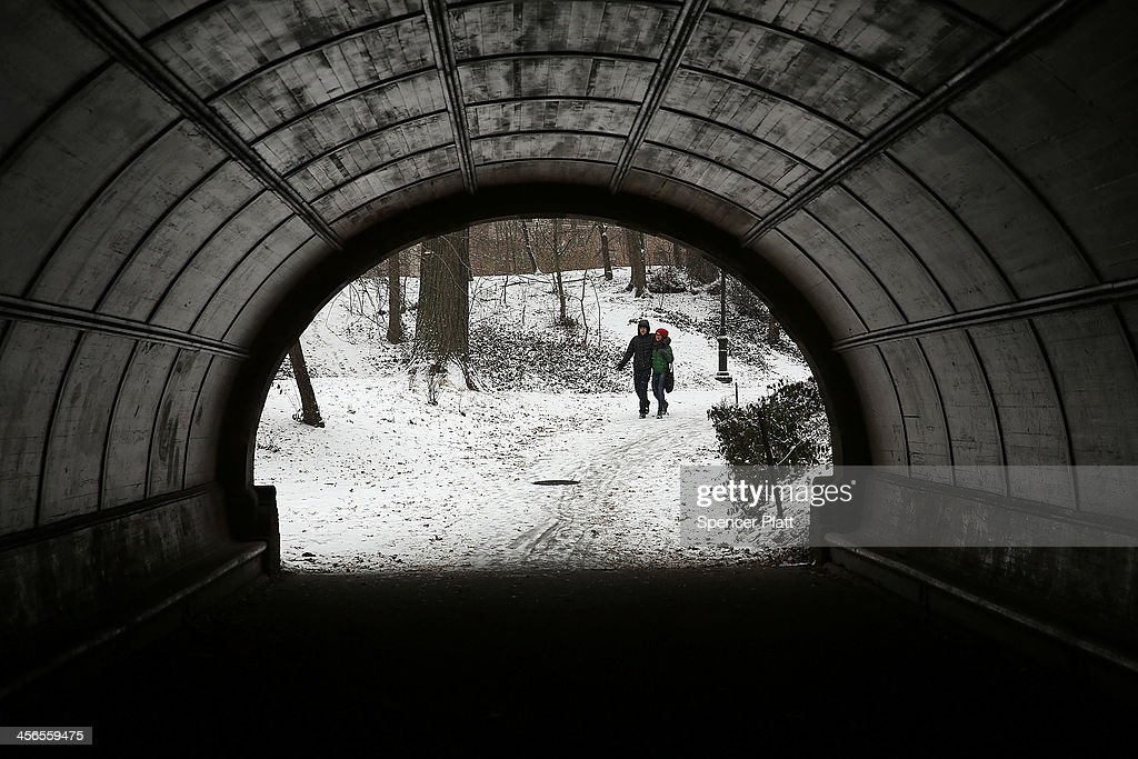 A couple walks through Prospect Park during a snow storm on December 14, 2013 in the Brooklyn borough of New York City. Much of the Northeast was hit by a storm stretching over 1,000 miles that could result in at least a foot of snow on parts of New England.