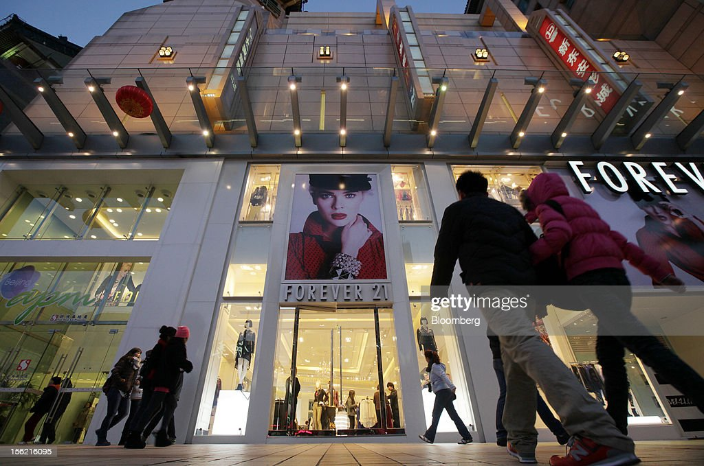 A couple walks toward a Forever 21 store at a shopping district in Beijing, China, on Sunday, Nov. 11, 2012. China's retail sales exceeded forecasts and inflation unexpectedly cooled to the slowest pace in 33 months, signaling the government is boosting growth without driving a rebound in prices. Photographer: Tomohiro Ohsumi/Bloomberg via Getty Images