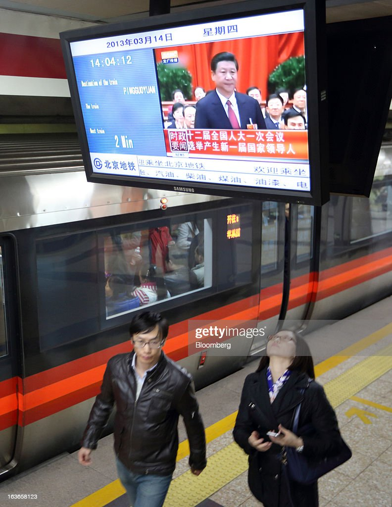 A couple walks under a television monitor displaying an image of <a gi-track='captionPersonalityLinkClicked' href=/galleries/search?phrase=Xi+Jinping&family=editorial&specificpeople=2598986 ng-click='$event.stopPropagation()'>Xi Jinping</a>, newly named president of China, during a news broadcast at a subway station in Beijing, China, on Thursday, March 14, 2013. Xi was named China's president by the national legislature, replacing Hu Jintao in the country's most rapid formal transfer of power in more than a generation. Photographer: Tomohiro Ohsumi/Bloomberg via Getty Images
