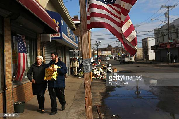 A couple walks with items discarded from a flooded store in the heavily damaged Rockaway neighborhood where a large section of the iconic boardwalk...