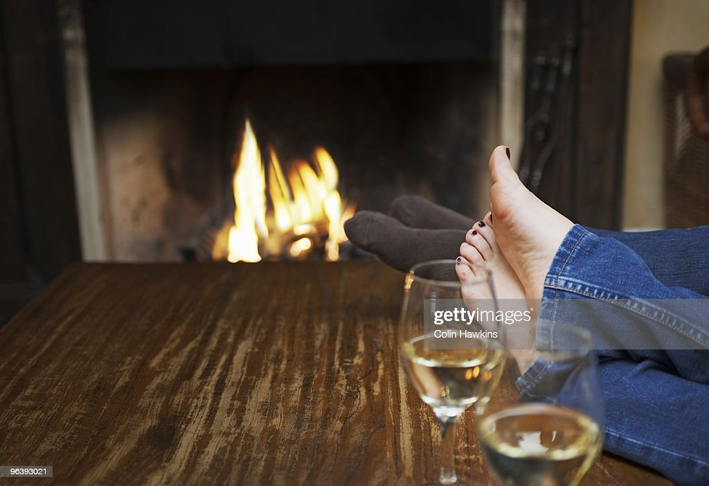couple warming feet in front of fire