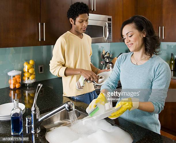 Couple washing dishes in kitchen, smiling
