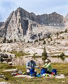 Couple washing dishes near high Sierra lake