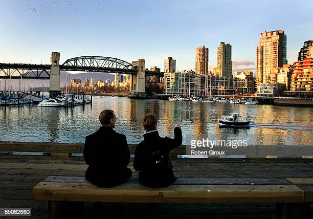 A couple watch a ferry boat approach from their seat on the Granville Island dock February 18 2009 in Vancouver British Columbia Canada Vancouver is...